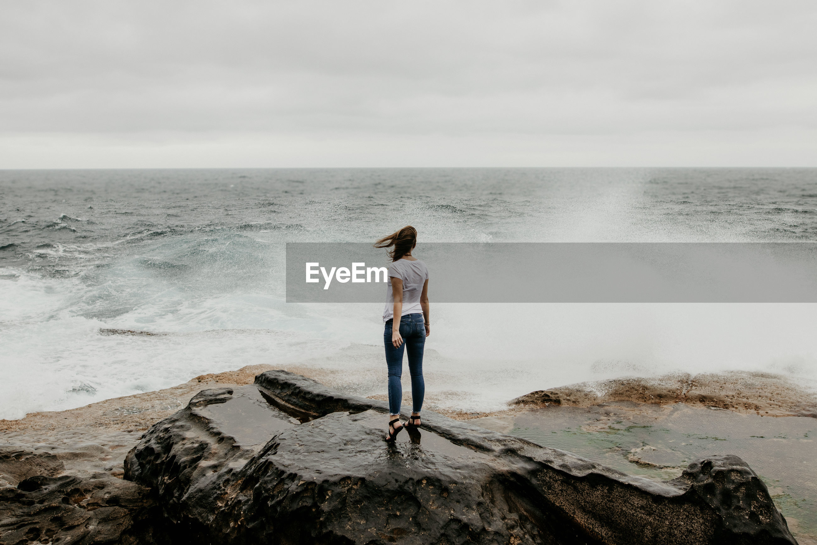 Rear view of woman standing on rock at beach