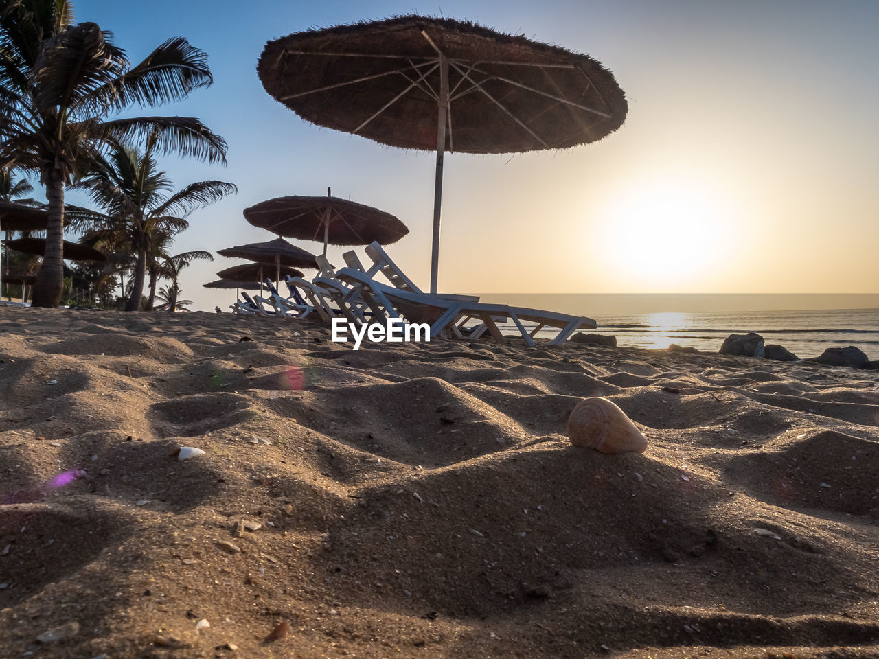 beach, sky, land, water, sea, nature, sunset, sand, tropical climate, palm tree, parasol, umbrella, beauty in nature, horizon over water, sunlight, sun, tree, scenics - nature, tranquility, outdoors, coconut palm tree