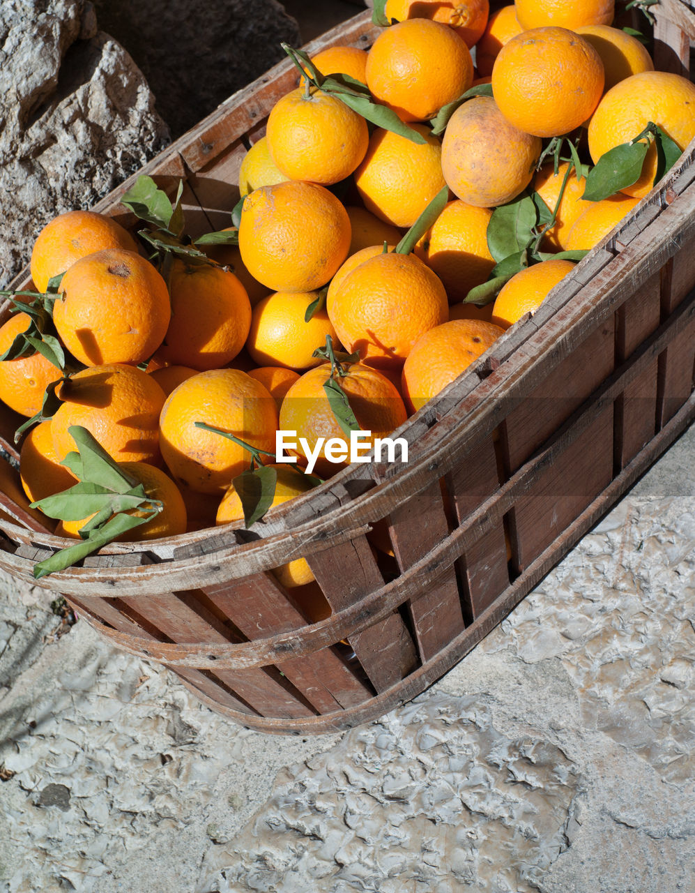 High angle view of fresh organic oranges in wooden basket