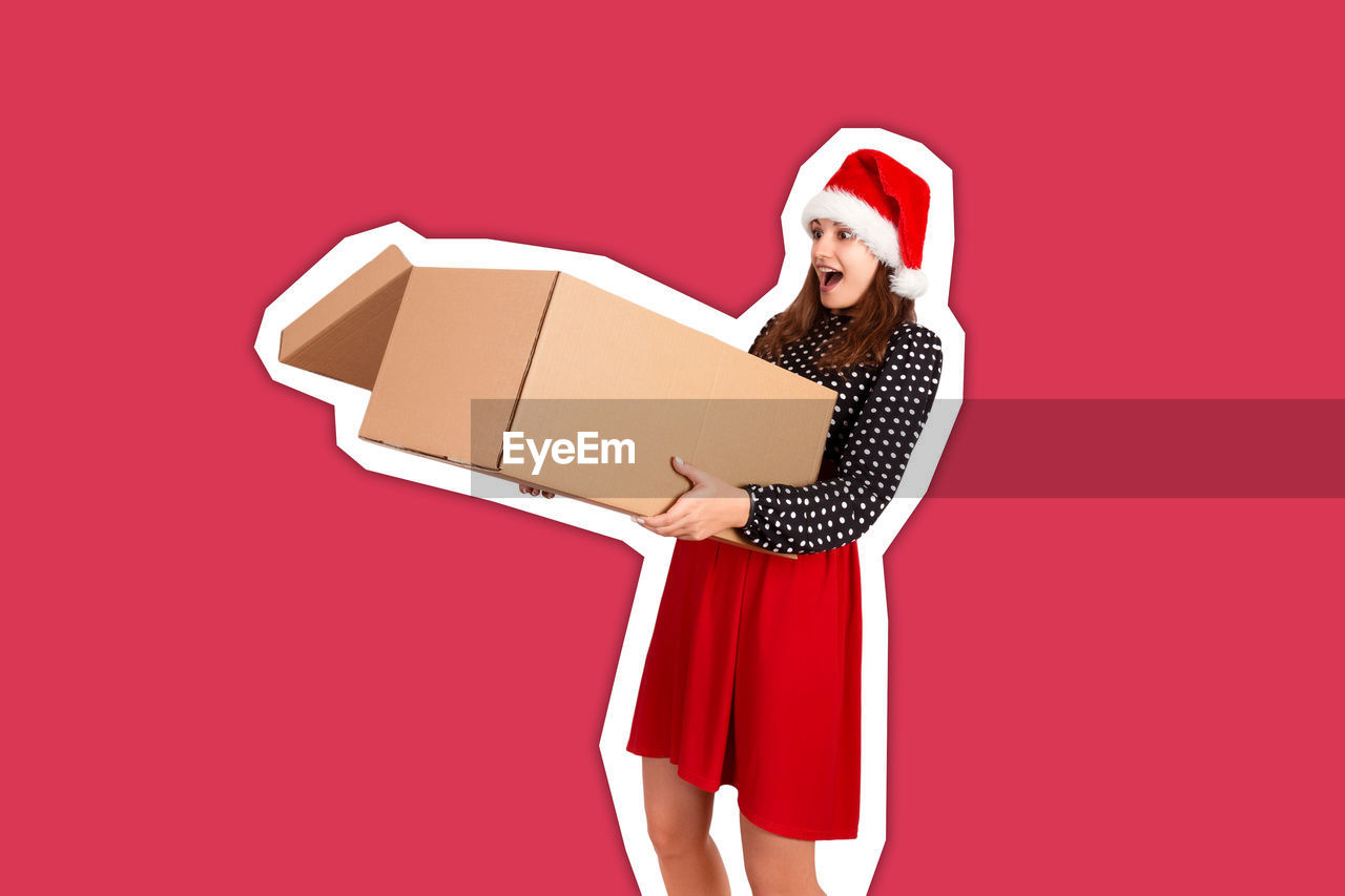 Young woman with mouth open holding cardboard box against red background