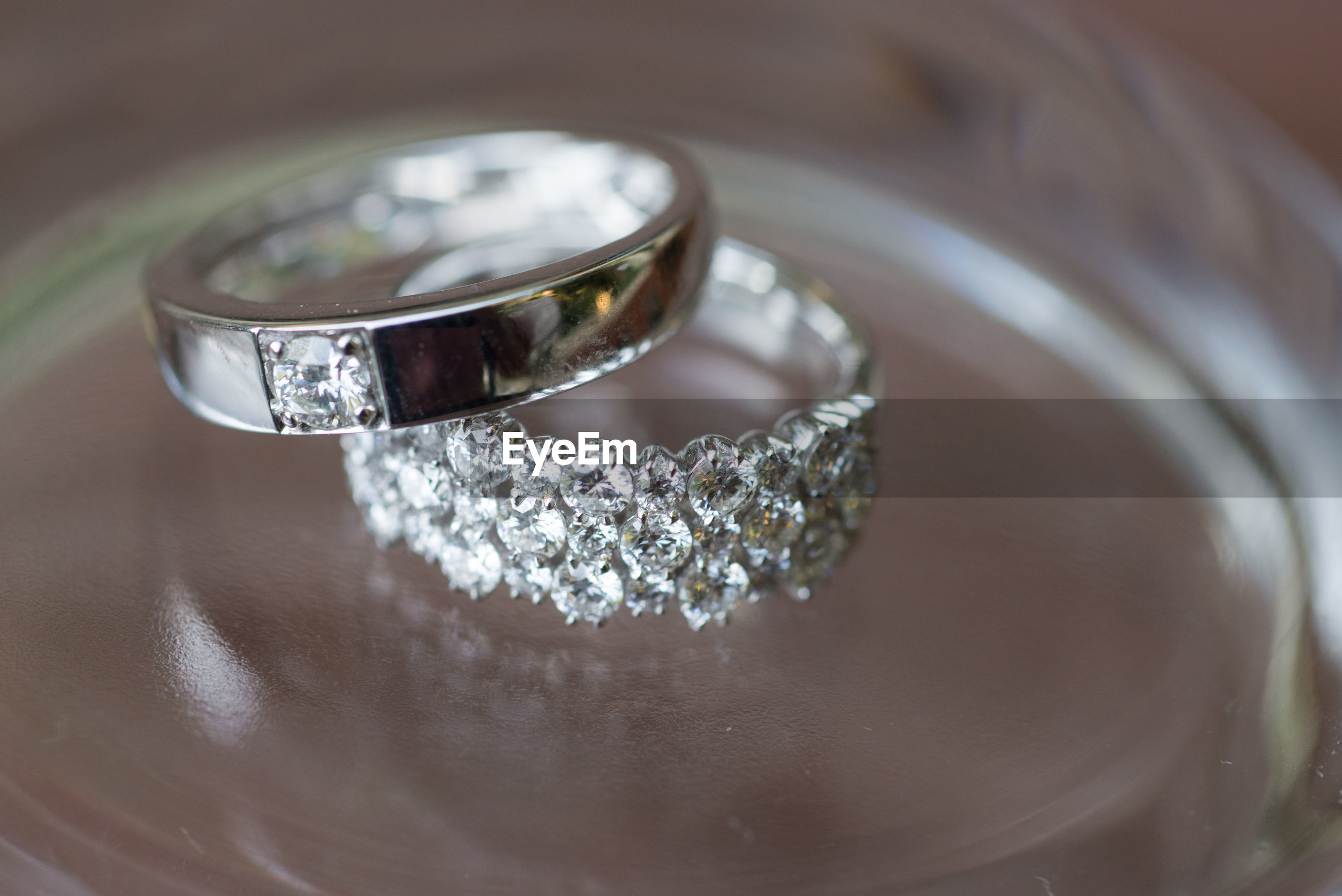 Close-up of wedding rings on glass table