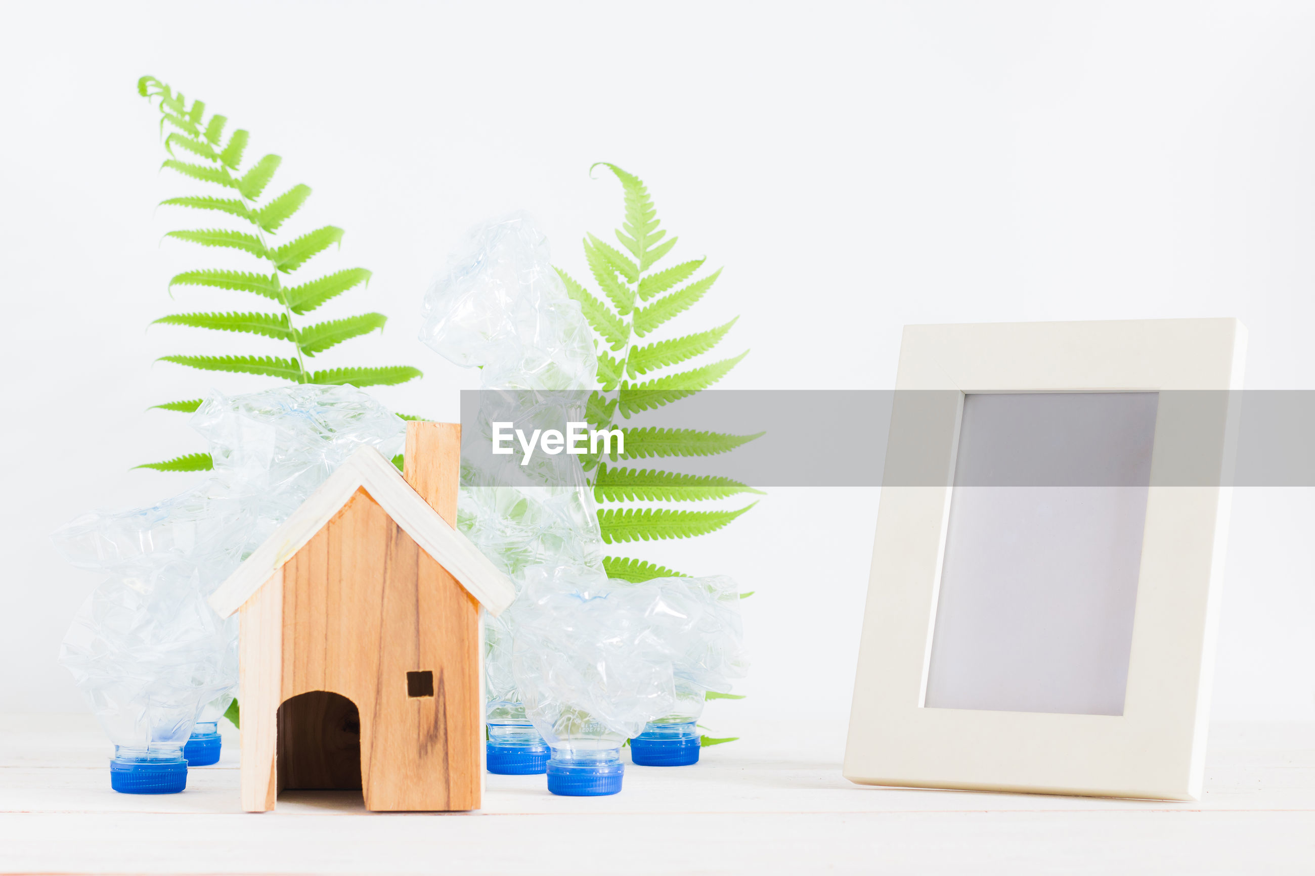 Close-up of model house with plant in plastic bottle with picture frame over white background