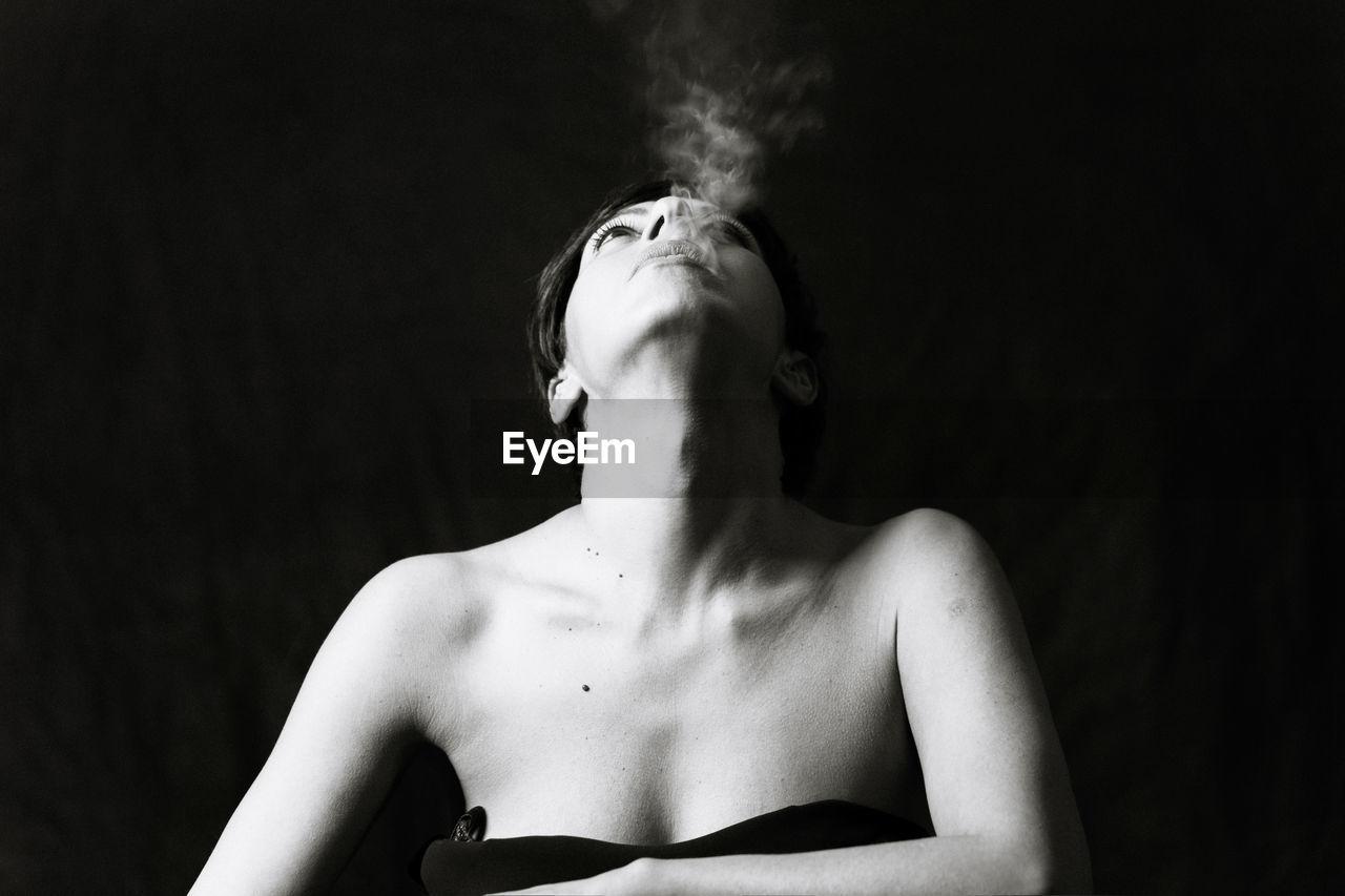 Close-Up Of Woman Smoking In Darkroom
