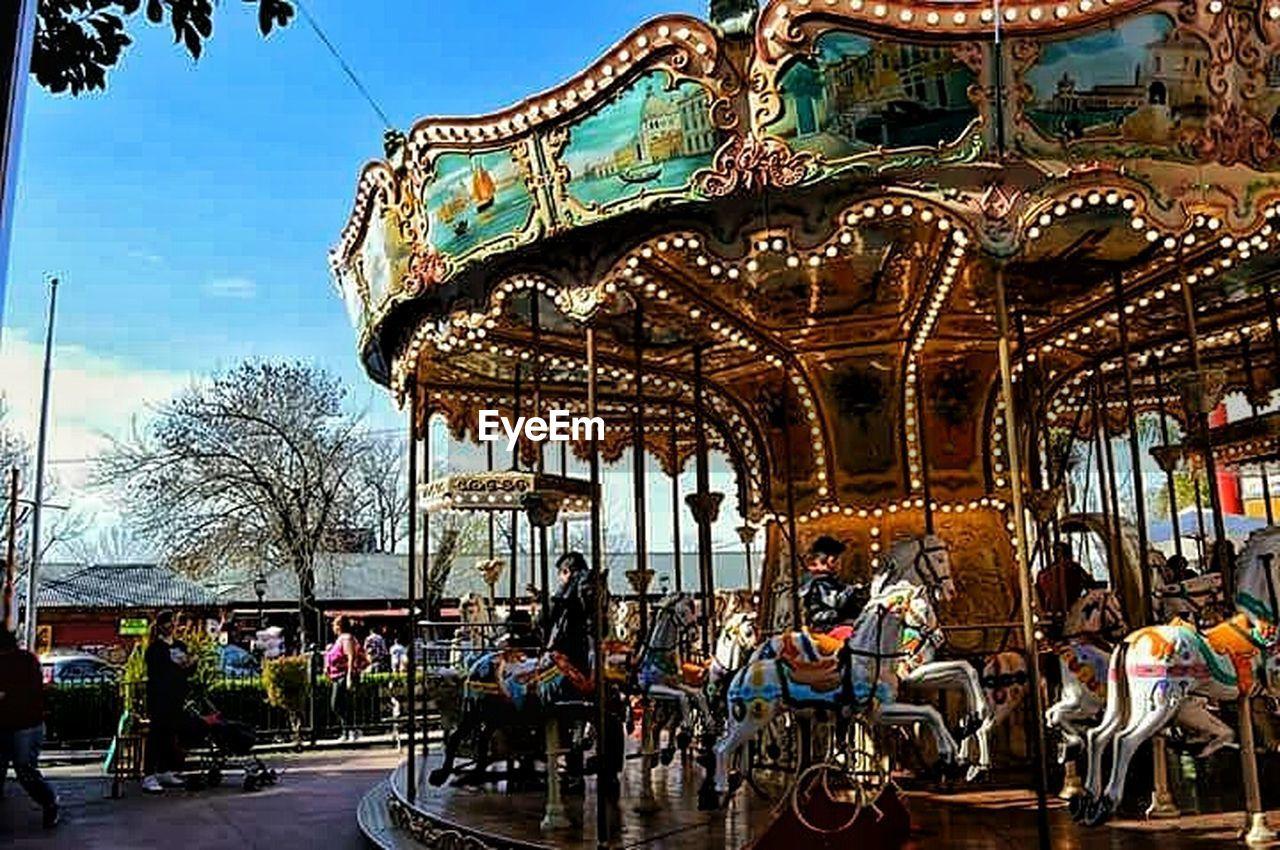 amusement park, arts culture and entertainment, carousel, amusement park ride, carousel horses, leisure activity, recreational pursuit, enjoyment, merry-go-round, day, outdoors, sky, people, adult