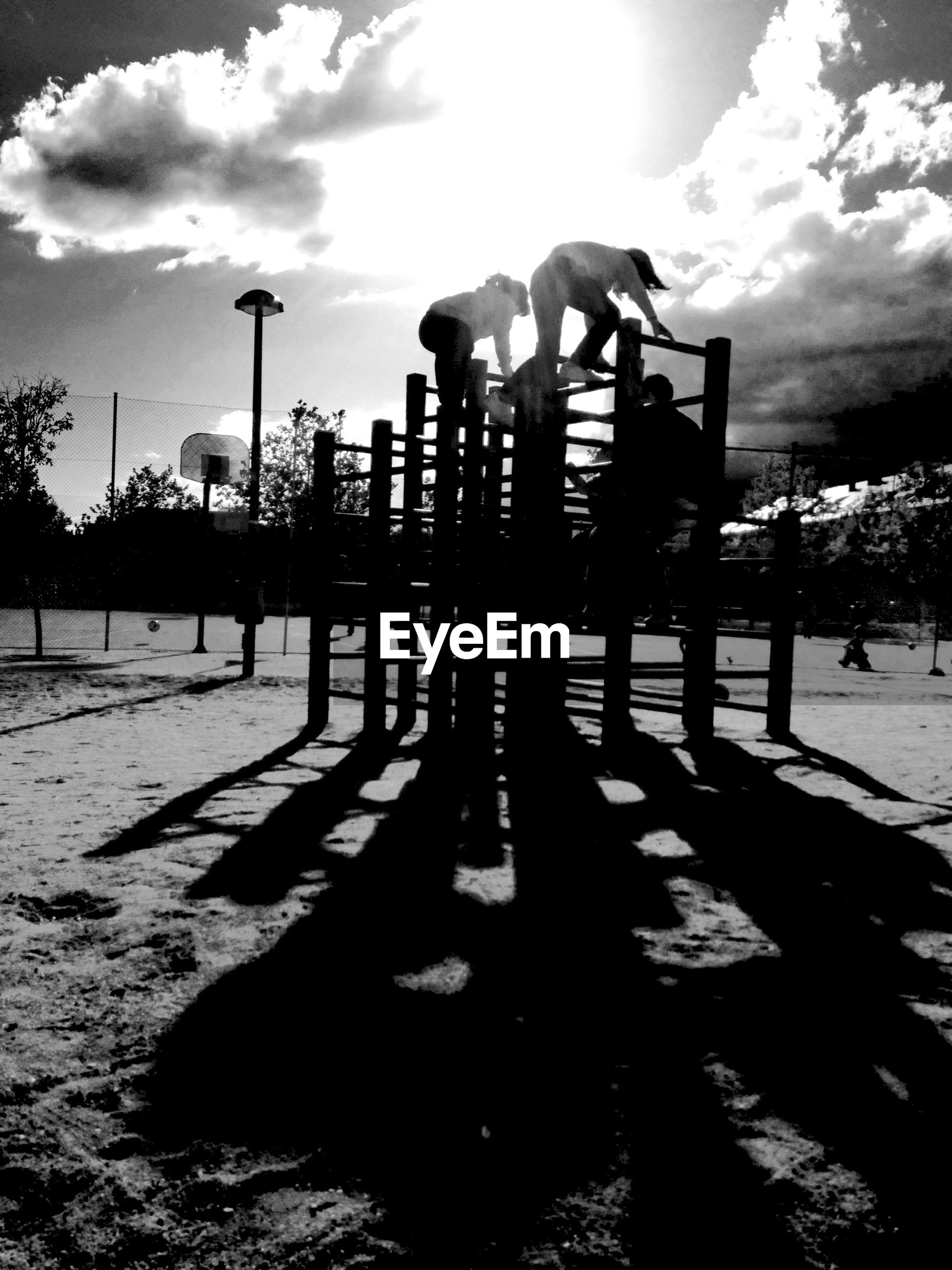 Children climbing on jungle gym against sky in park