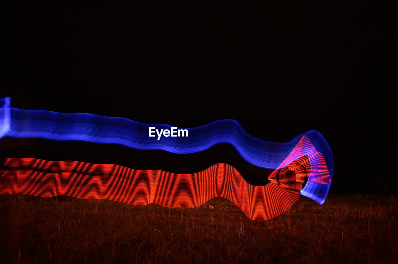 MULTI COLORED LIGHT PAINTING AGAINST SKY