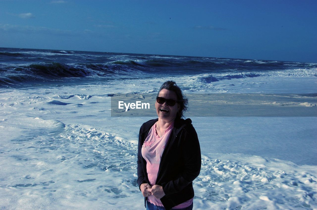 Portrait of woman in sunglass standing at beach against sky