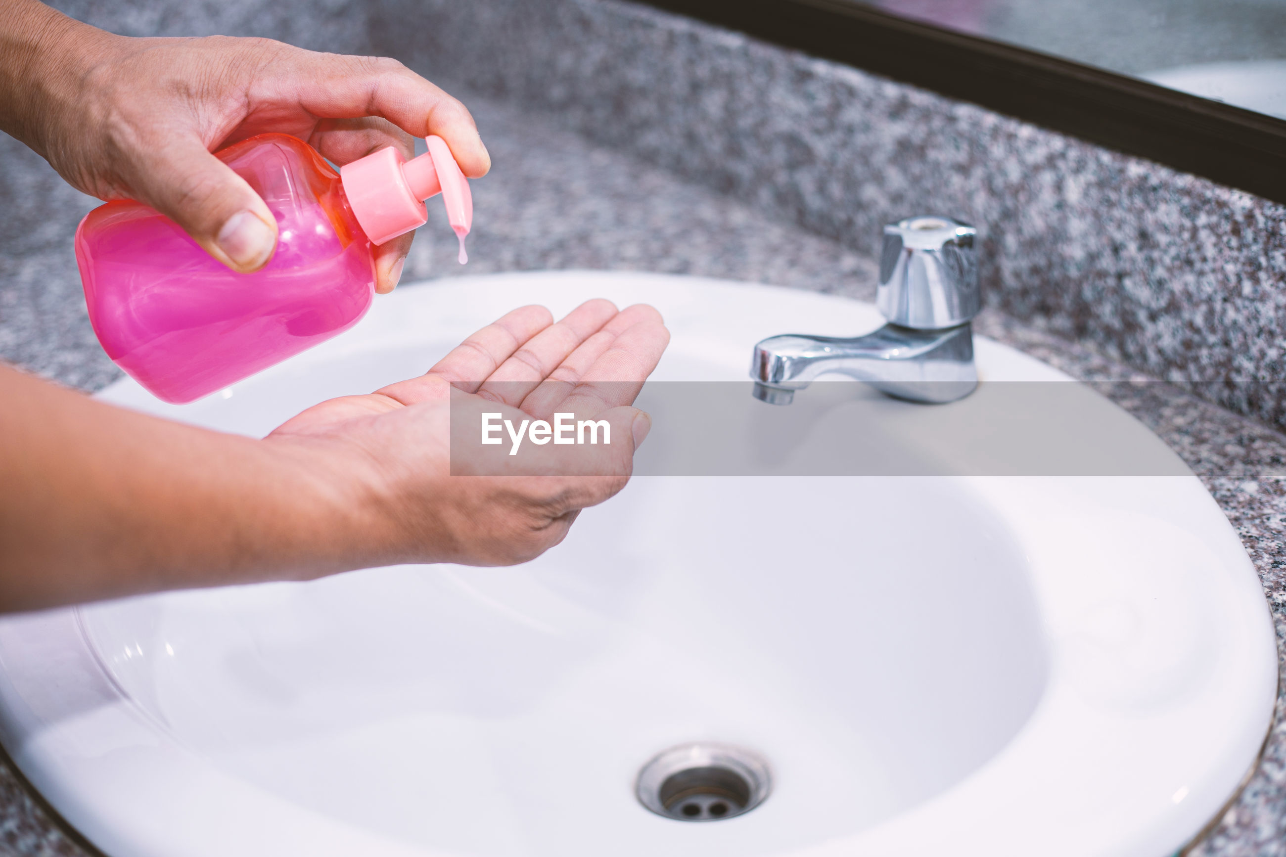 HIGH ANGLE VIEW OF MAN HAND HOLDING WATER IN BATHROOM