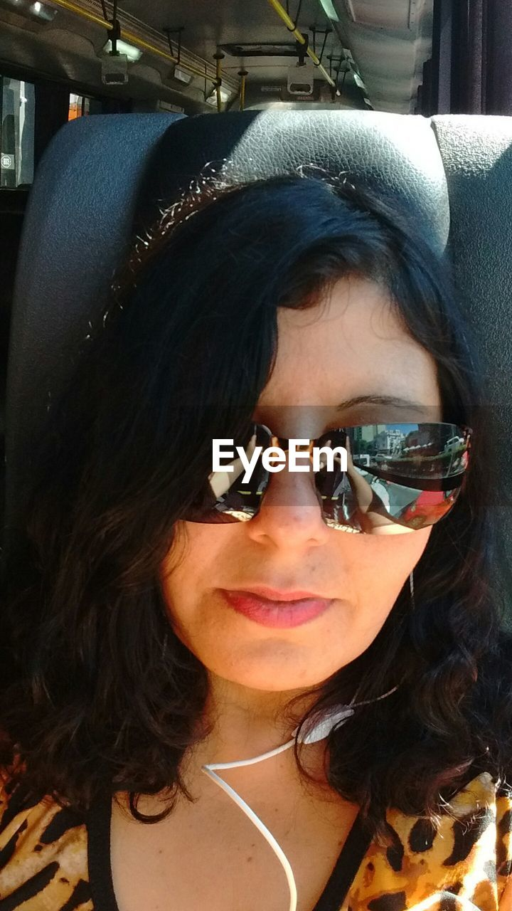 Close-up of woman with sunglasses sitting in bus