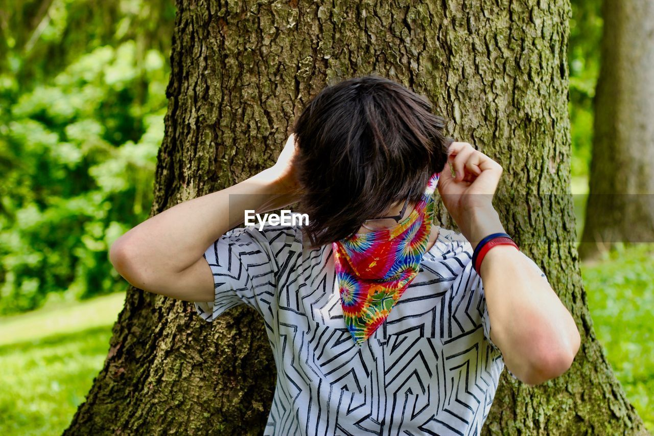plant, tree trunk, trunk, tree, real people, one person, leisure activity, nature, day, lifestyles, growth, land, women, hair, casual clothing, green color, hairstyle, rear view, focus on foreground, outdoors