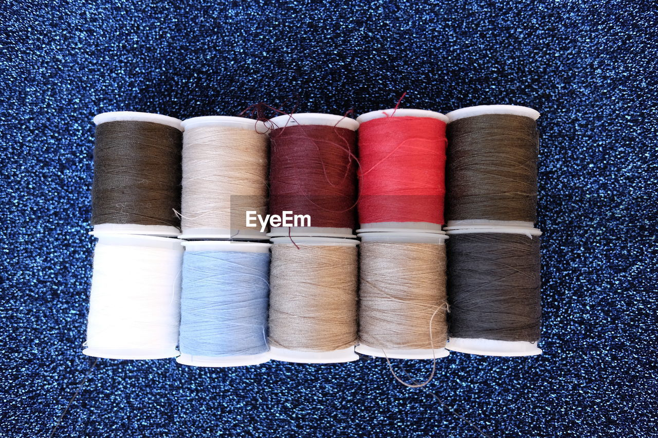 Close-Up Of Colorful Thread Spool On Fabric