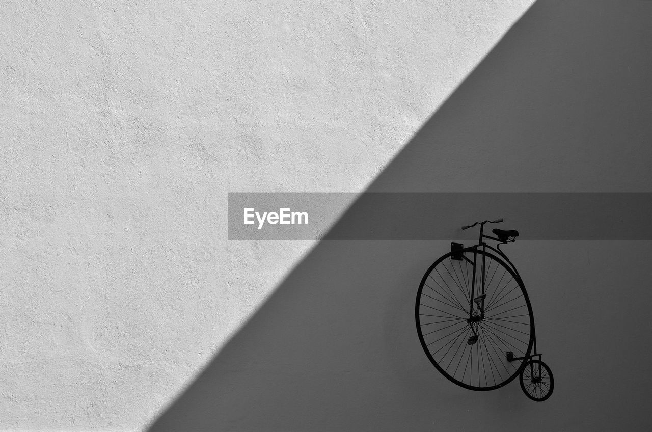 wall - building feature, bicycle, built structure, architecture, transportation, land vehicle, no people, mode of transportation, shadow, wheel, sunlight, building exterior, wall, day, nature, outdoors, stationary, shape, white color, geometric shape, tire, spoke, focus on shadow