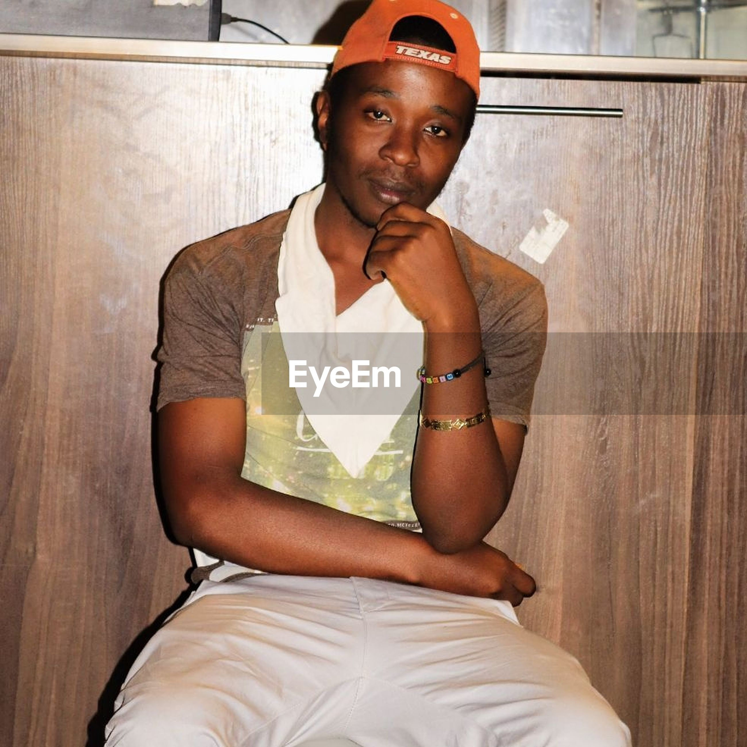 one person, real people, front view, looking at camera, portrait, indoors, sitting, young adult, lifestyles, three quarter length, casual clothing, leisure activity, young men, looking, wood - material, contemplation