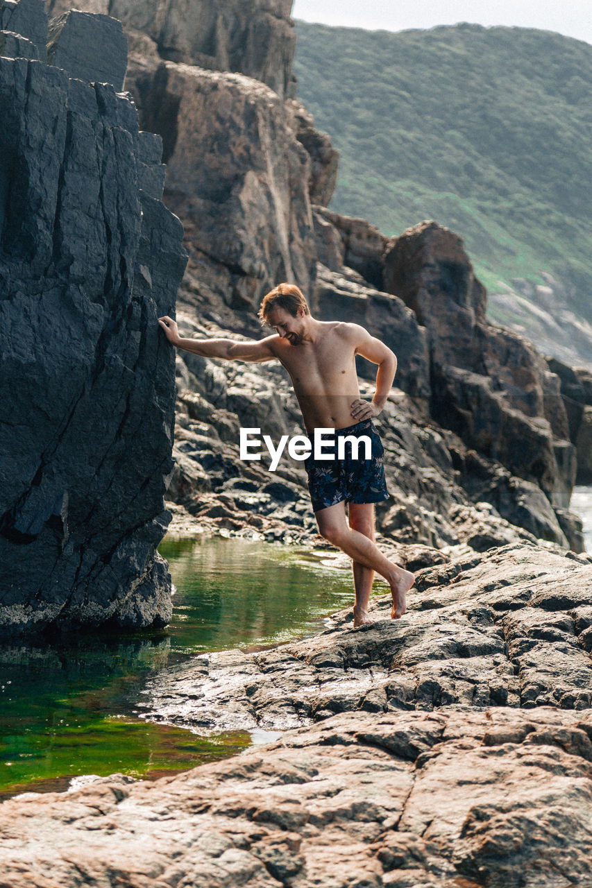 Full length of shirtless man standing on rock at beach