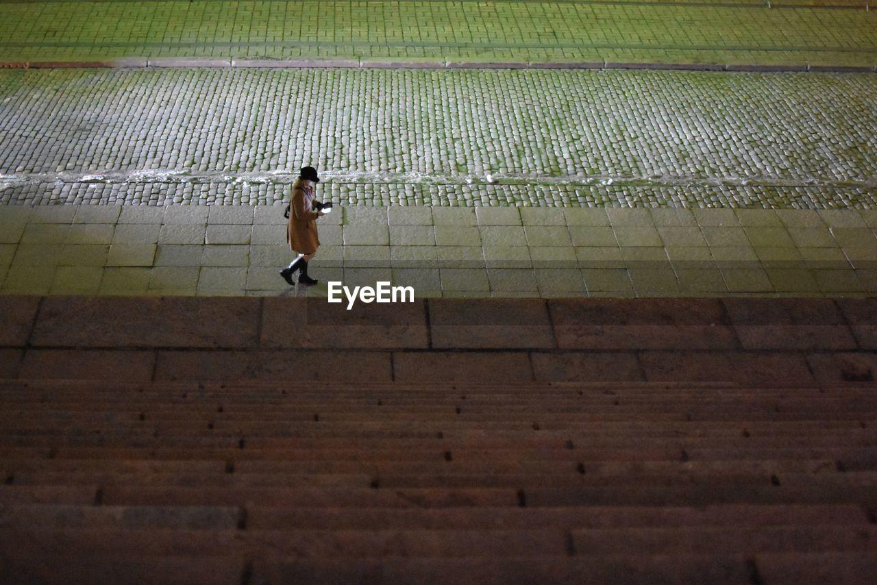 Full Length Of Woman Walking On Sidewalk