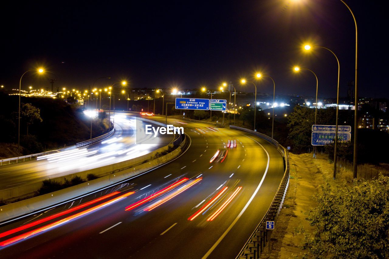 illuminated, night, long exposure, speed, street, light trail, motion, road, blurred motion, transportation, city, street light, lighting equipment, no people, nature, sky, architecture, glowing, high angle view, curve, outdoors, light, multiple lane highway