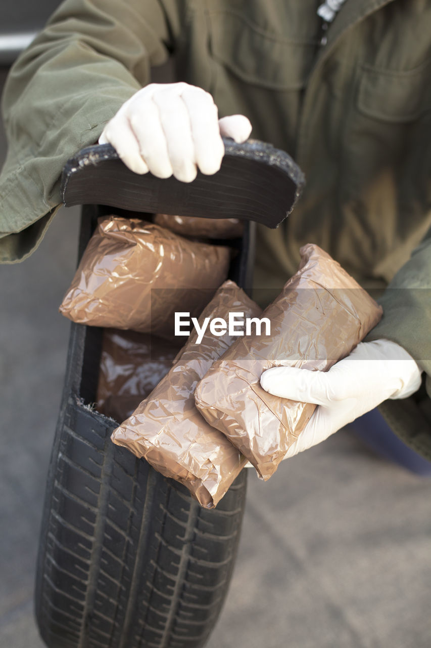 Low Section Of Man Holding Cocaine Parcels In Tire