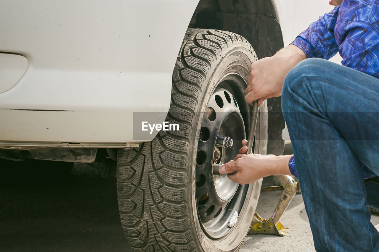 Cropped Image Of Mechanic Inflating Car Tire