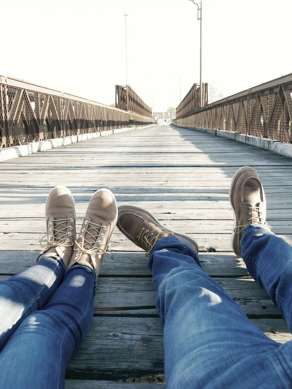 low section, human leg, personal perspective, shoe, human body part, real people, body part, jeans, transportation, architecture, men, sky, built structure, day, casual clothing, bridge, people, lifestyles, connection, leisure activity, bridge - man made structure, outdoors, human foot