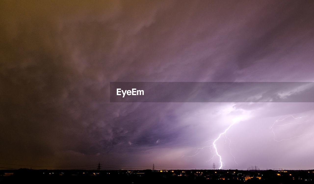 thunderstorm, lightning, storm, weather, dramatic sky, power in nature, storm cloud, forked lightning, night, cloud - sky, sky, danger, beauty in nature, nature, architecture, built structure, no people, illuminated, scenics, outdoors, cityscape, building exterior, city