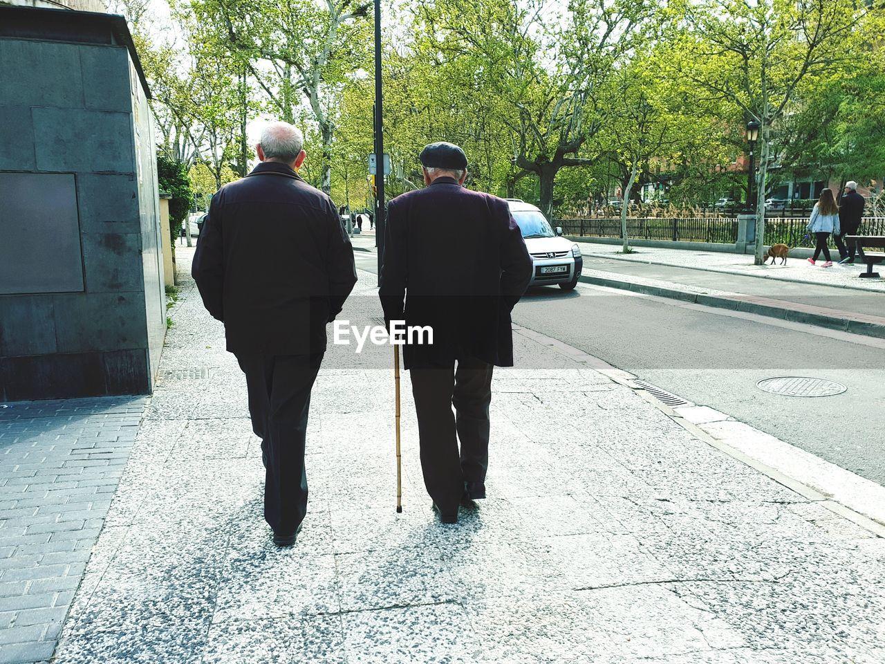 REAR VIEW OF MEN WALKING ON ROAD