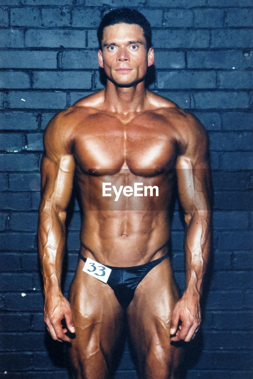 muscular build, healthy lifestyle, looking at camera, portrait, strength, exercising, athlete, adult, wellbeing, body building, lifestyles, sports training, sport, vitality, one person, confidence, front view, beautiful people, males, men, weight training, abdominal muscle, human muscle, brick, chest, effort