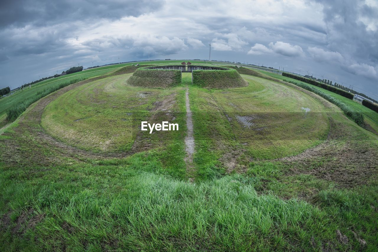 cloud - sky, nature, sky, field, grass, scenics, beauty in nature, day, green color, tranquil scene, outdoors, landscape, tranquility, transportation, no people, high angle view, rural scene, winding road, fish-eye lens