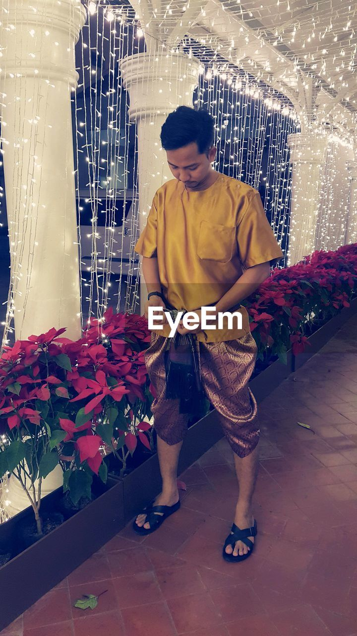 real people, one person, full length, plant, flower, flowering plant, lifestyles, indoors, men, casual clothing, standing, leisure activity, young men, front view, young adult, holding, nature, decoration, looking, flower arrangement, bouquet
