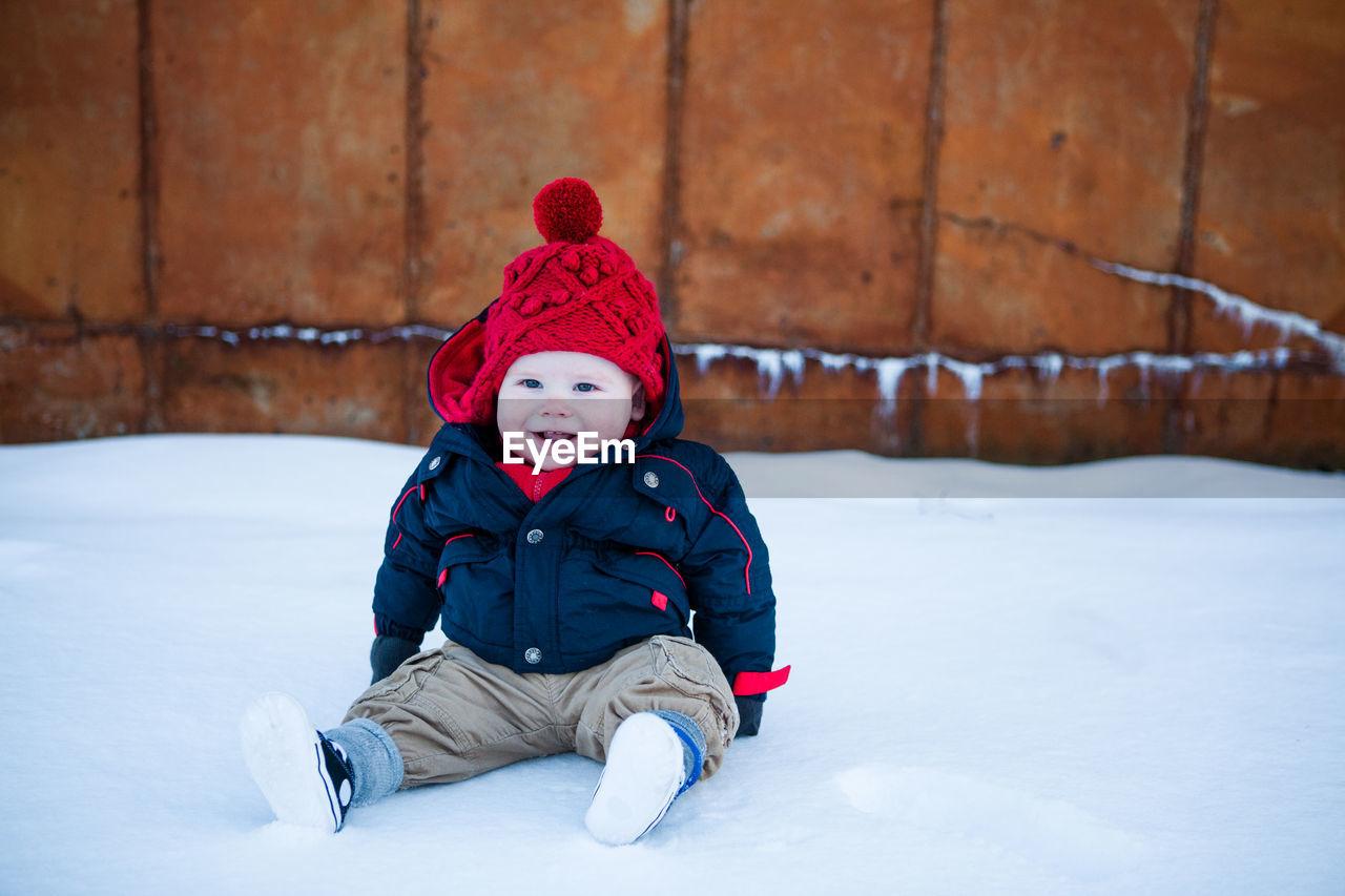 Cute Boy In Warm Clothing On Snow