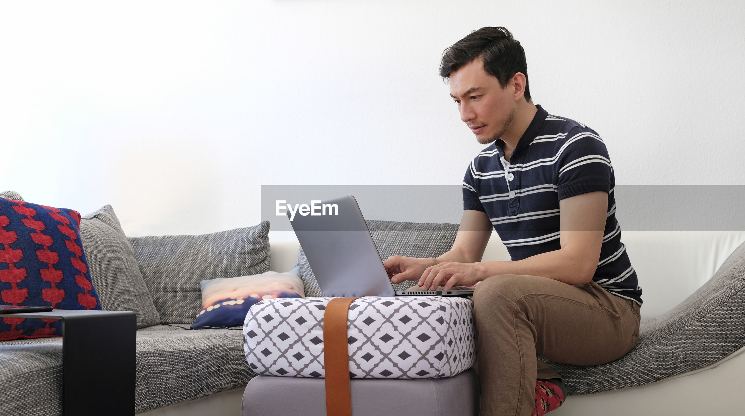 Man using laptop while sitting on sofa at home