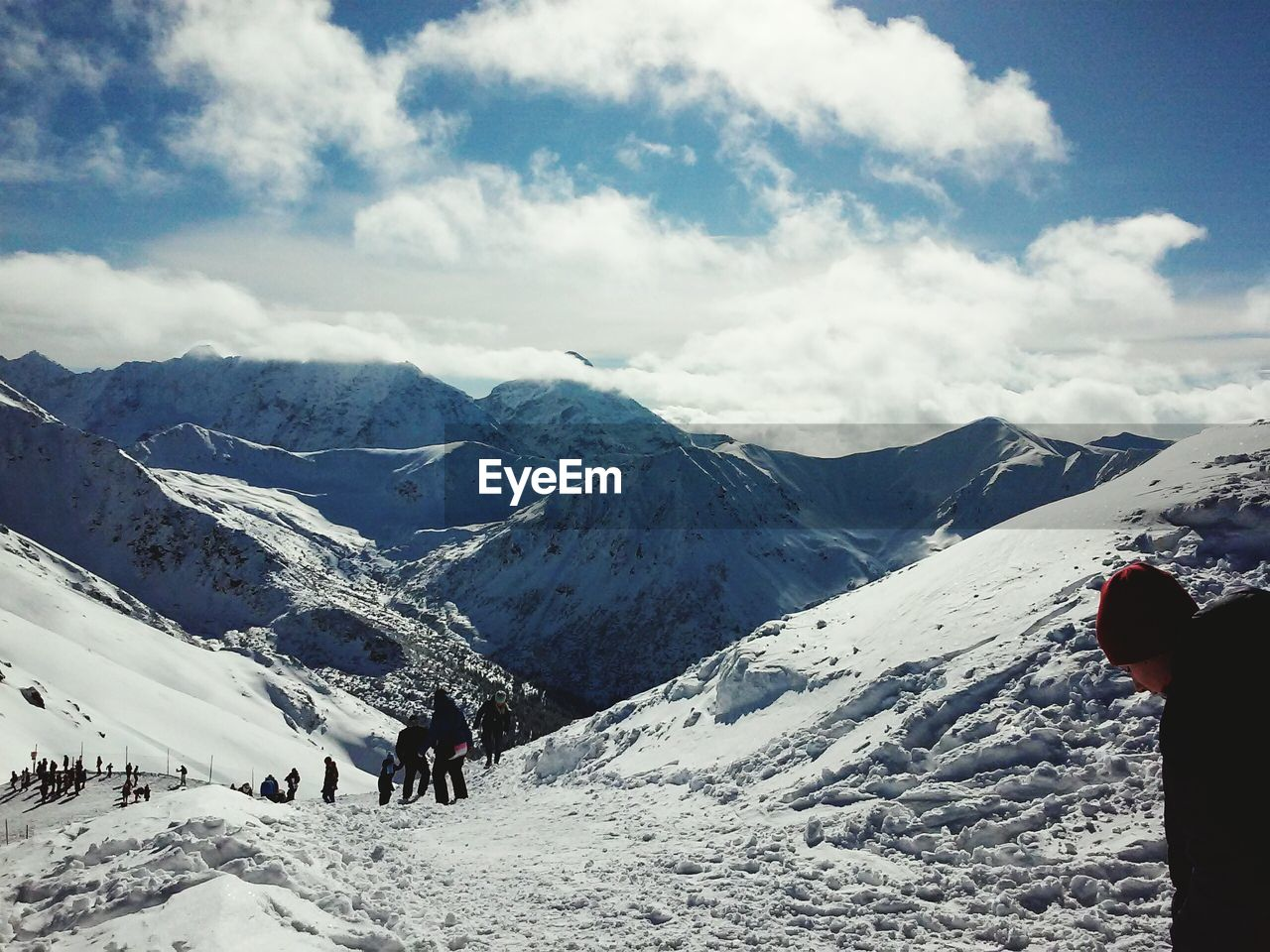 People standing on snowcapped mountains against cloudy sky