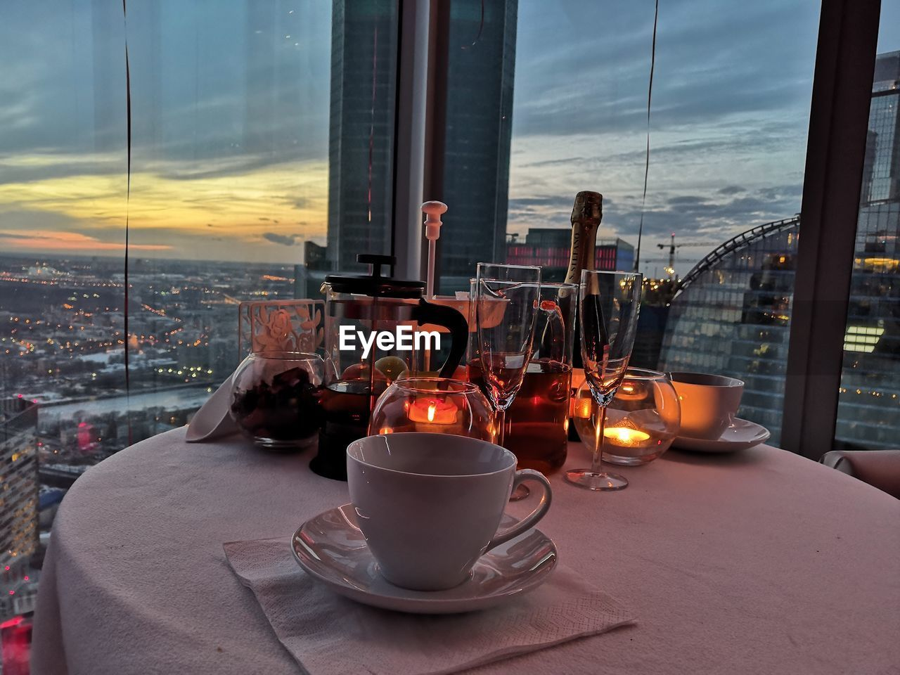 food and drink, table, drink, cup, transparent, window, architecture, indoors, glass - material, sky, city, saucer, refreshment, mug, nature, restaurant, cityscape, business, no people, crockery, glass