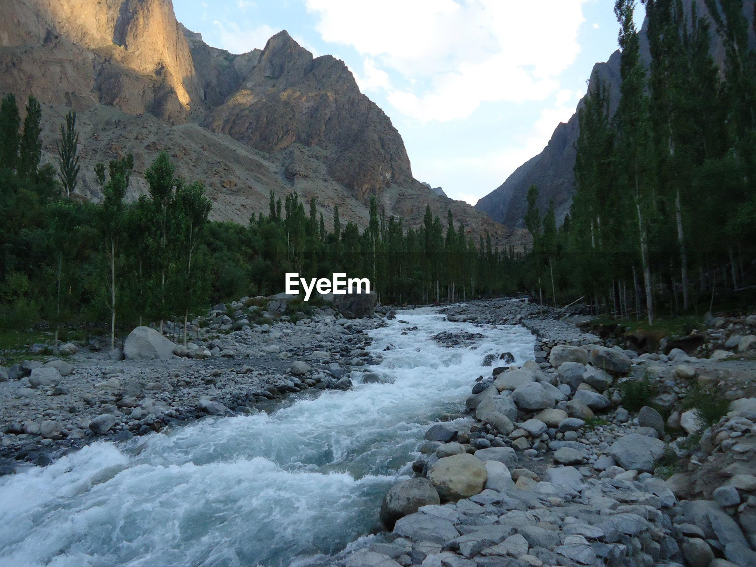 Scenic view of river stream amidst rocks against sky