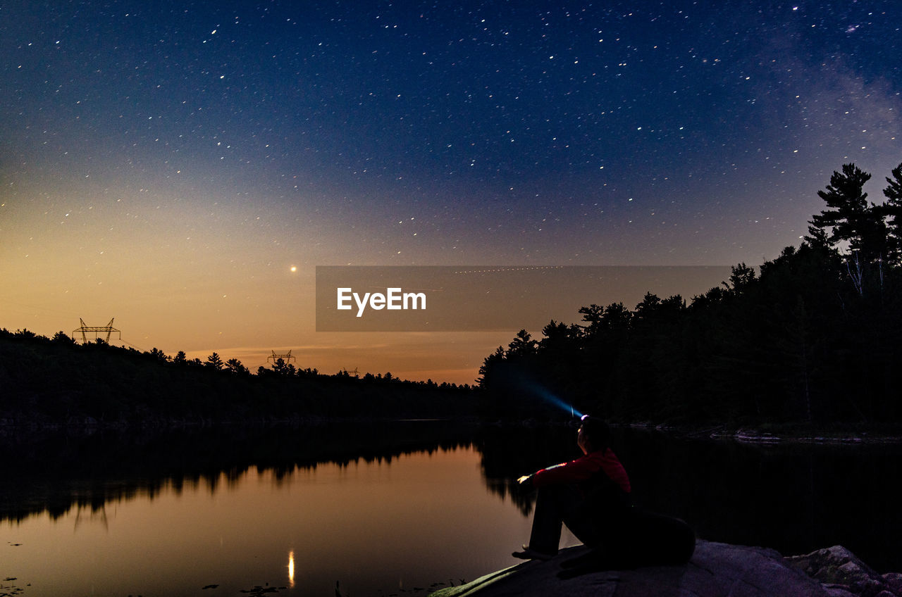 sky, lake, water, beauty in nature, scenics - nature, real people, star - space, night, tranquility, one person, tree, tranquil scene, nature, space, sitting, plant, silhouette, reflection, lifestyles, astronomy