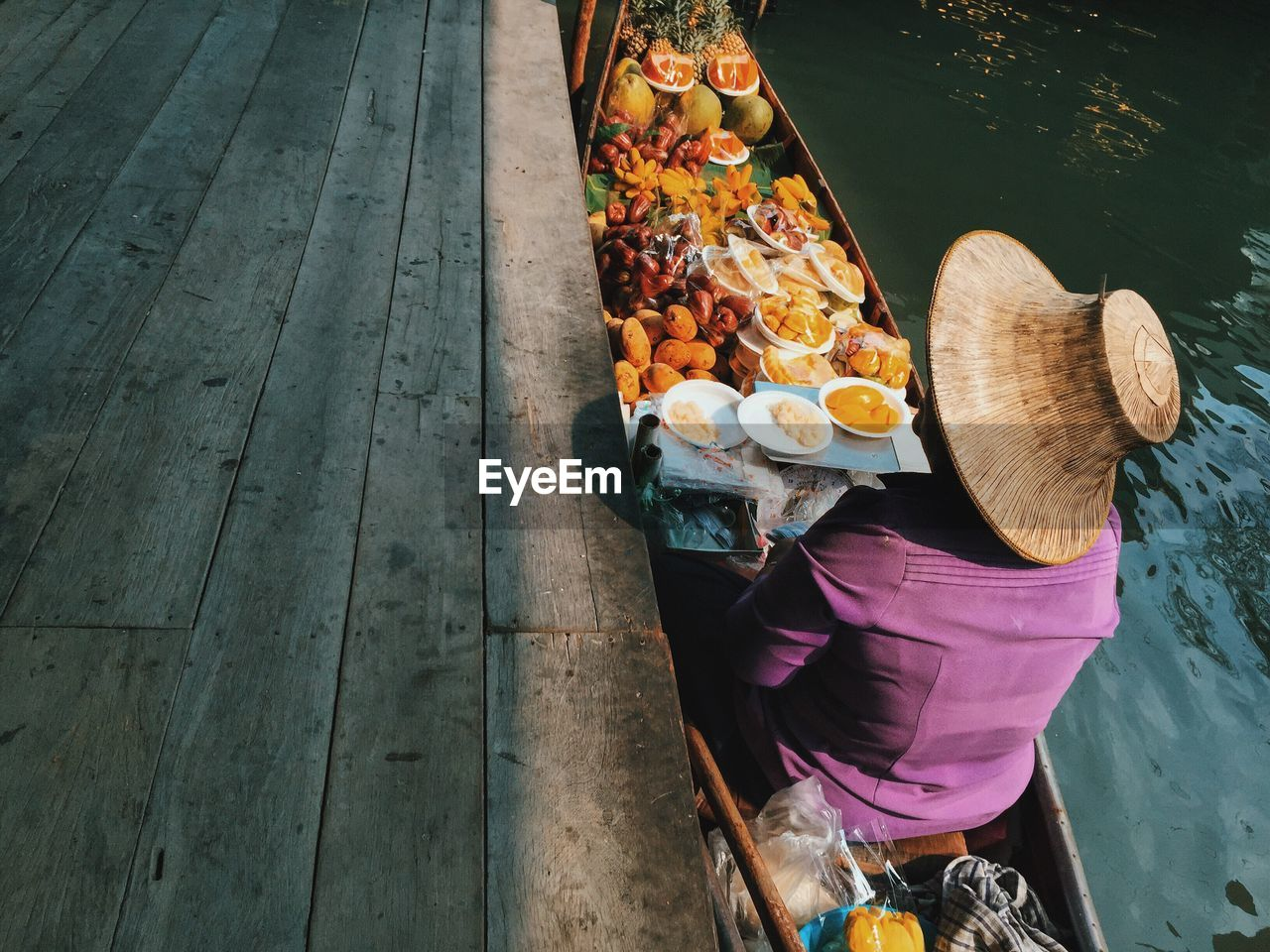 Person in boat with fruits at damnoen saduak floating market