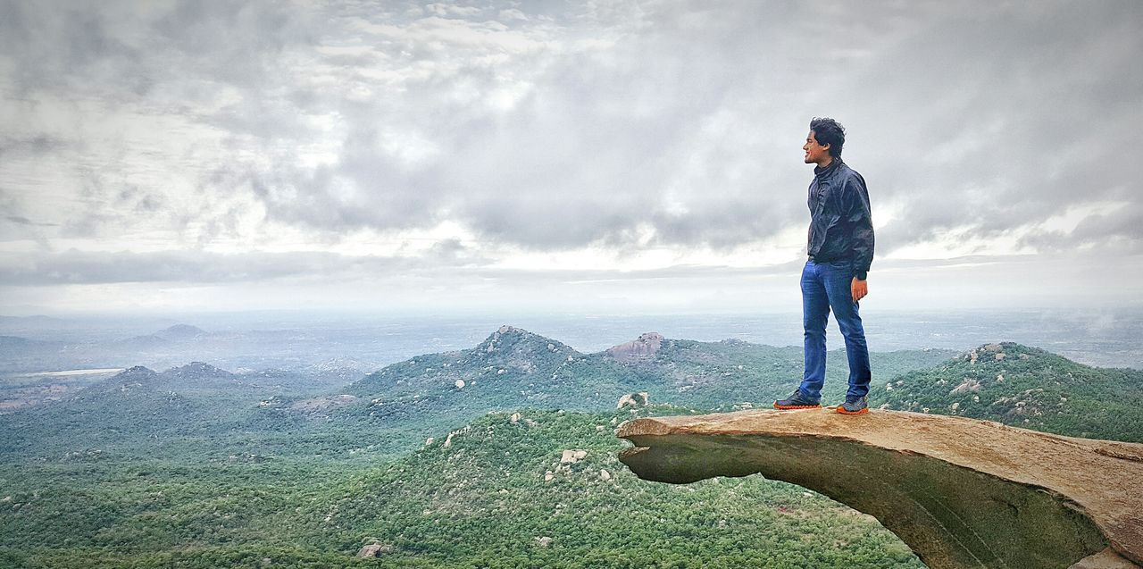 Man standing on top of avalabetta hilltop against cloudy sky