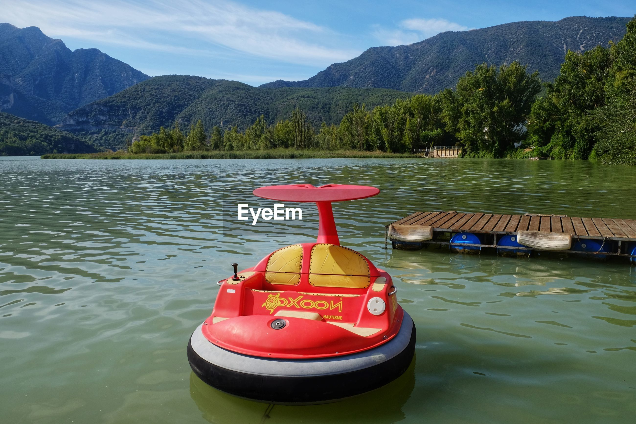 RED FLOATING ON LAKE AGAINST MOUNTAIN