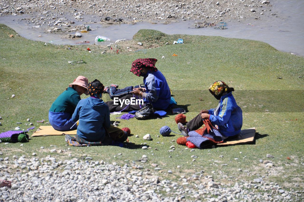 People knitting wool on field