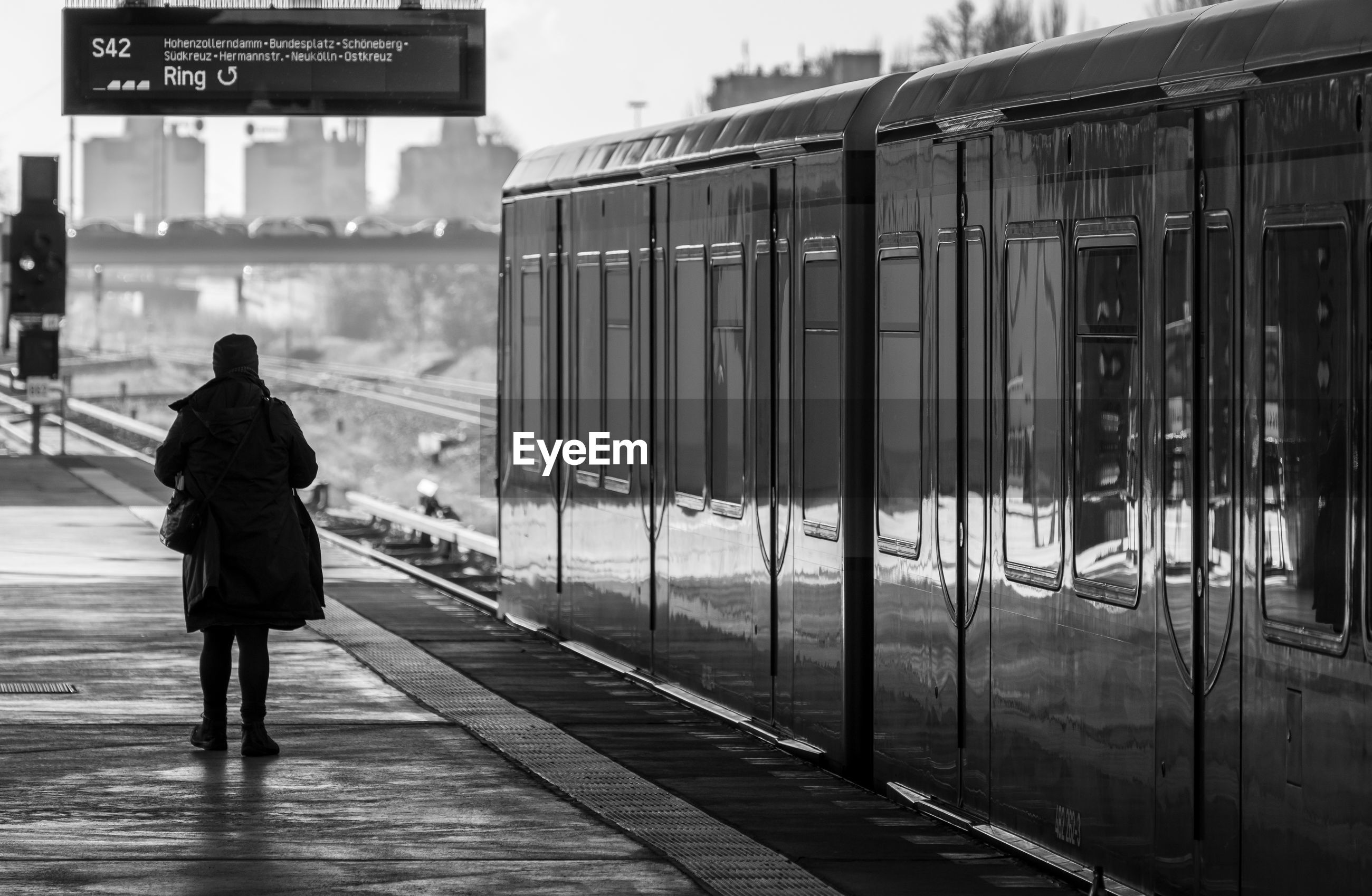 Rear view of silhouette woman standing on railroad station platform