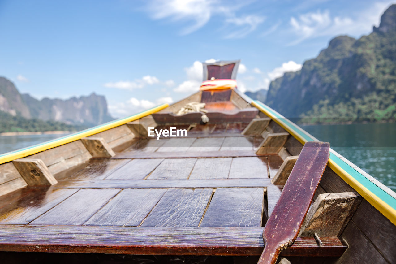 water, nature, architecture, mountain, sky, built structure, wood - material, nautical vessel, no people, day, focus on foreground, lake, outdoors, transportation, building exterior, travel destinations, table