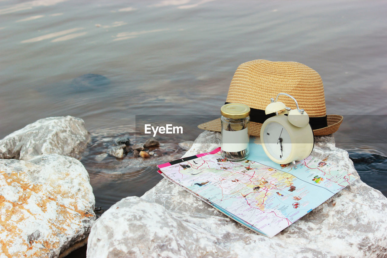 water, rock, solid, rock - object, day, nature, no people, sea, still life, land, beach, outdoors, cup, high angle view, creativity, drink, focus on foreground, representation, art and craft