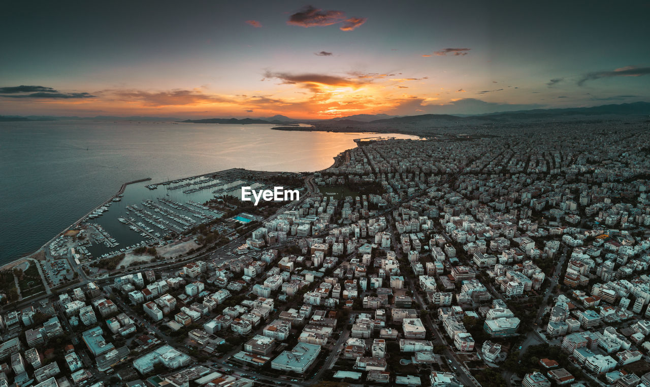 Aerial View Of Sea By Cityscape During Sunset