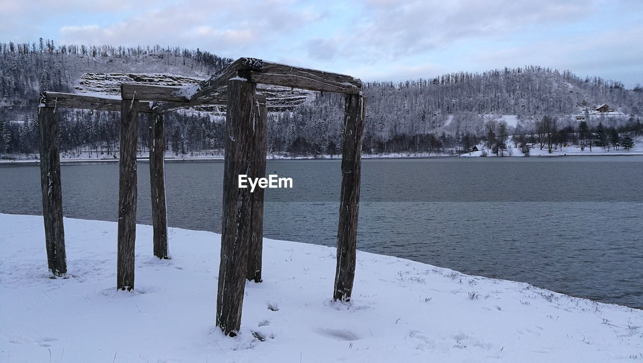 cold temperature, winter, snow, weather, nature, outdoors, sky, tranquility, scenics, no people, day, tranquil scene, beauty in nature, tree, frozen, water, lake, wooden post, landscape, bare tree