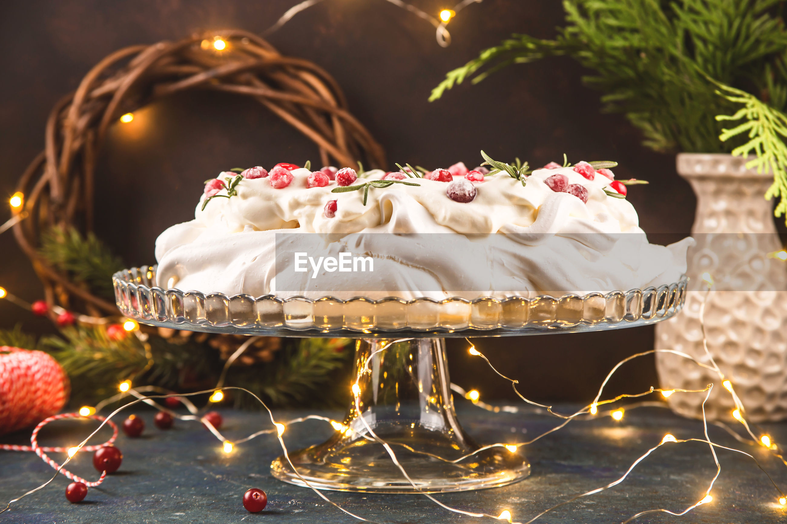 View of cake with plant and christmas lighting on table