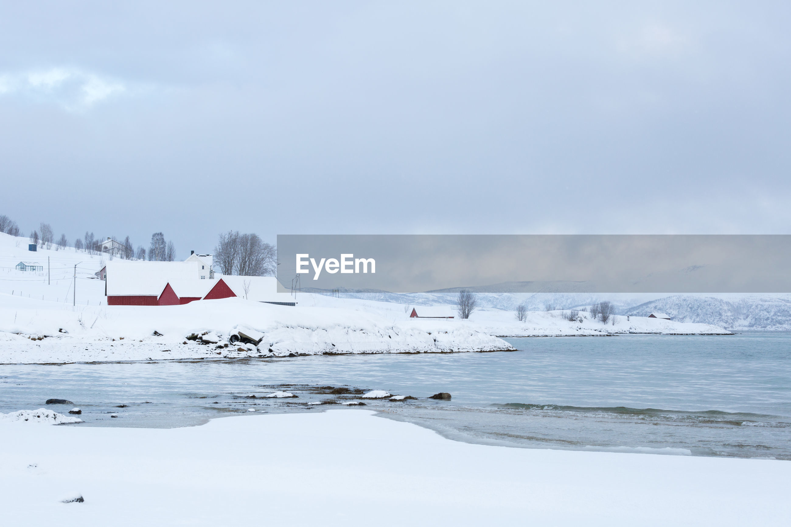 Snow covered field by lake against sky