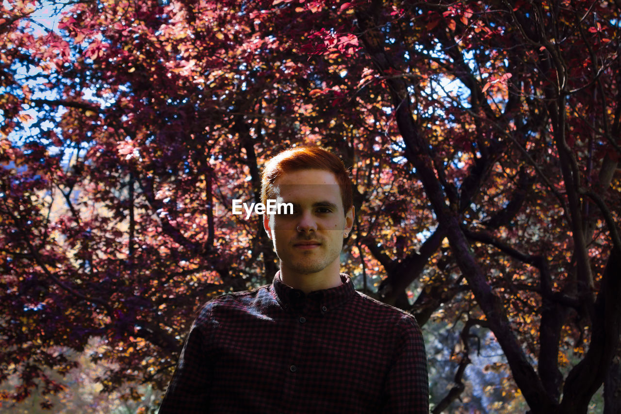 Portrait of young man standing against trees