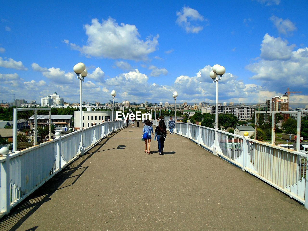 sky, real people, architecture, built structure, cloud - sky, lifestyles, two people, men, women, leisure activity, nature, adult, building exterior, people, full length, day, togetherness, rear view, street light, railing, bridge - man made structure, outdoors, diminishing perspective