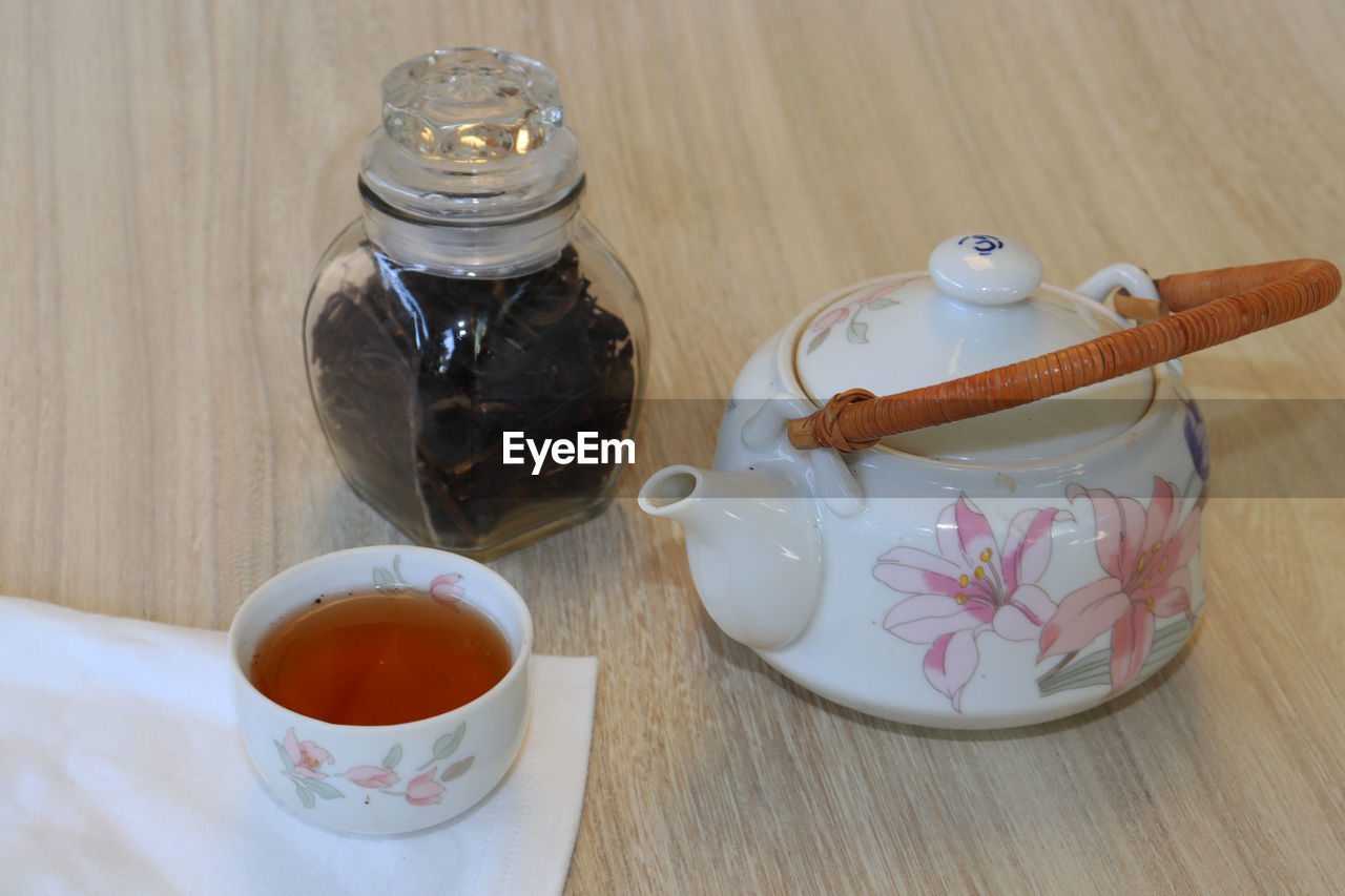 drink, food and drink, refreshment, cup, table, indoors, mug, tea, container, food, hot drink, tea - hot drink, teapot, no people, wood - material, jar, high angle view, glass - material, close-up, tea cup, crockery