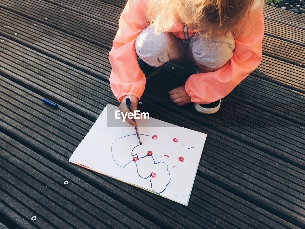 High Angle View Of Baby Girl Drawing While Crouching Outdoors
