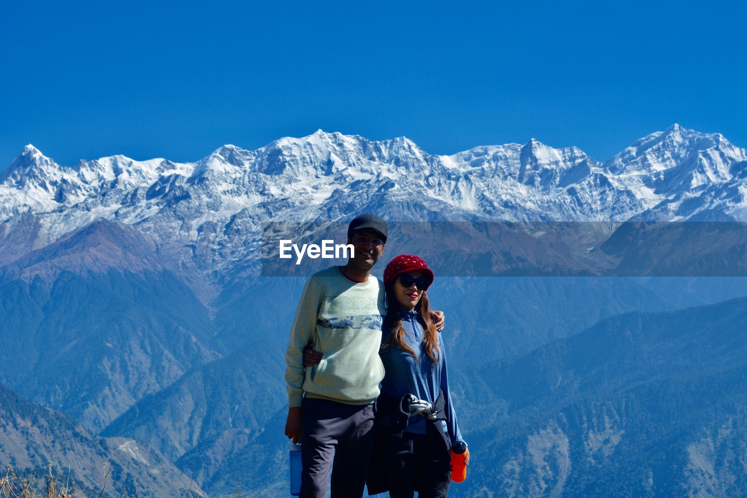 Portrait of couple standing against snowcapped mountains